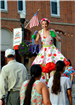 Girl on stilts waving to event goers