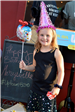 Girl in birthday hat holding happy birthday balloon
