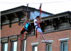 Two girls riding the zipline high above 5th Street