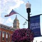 Photo light pole with flag banner and flowers