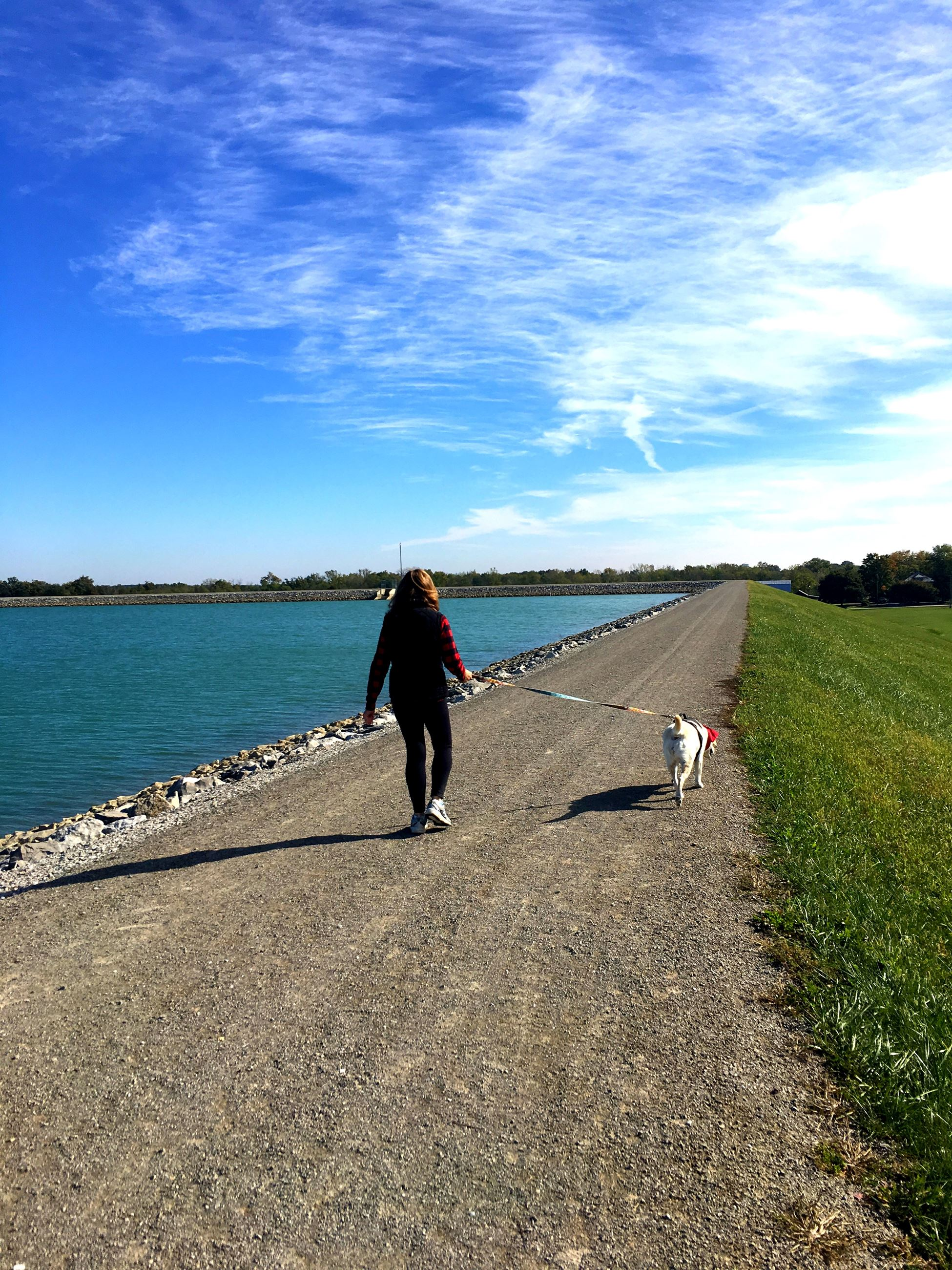 Photo of lady walking her dog at reservoir