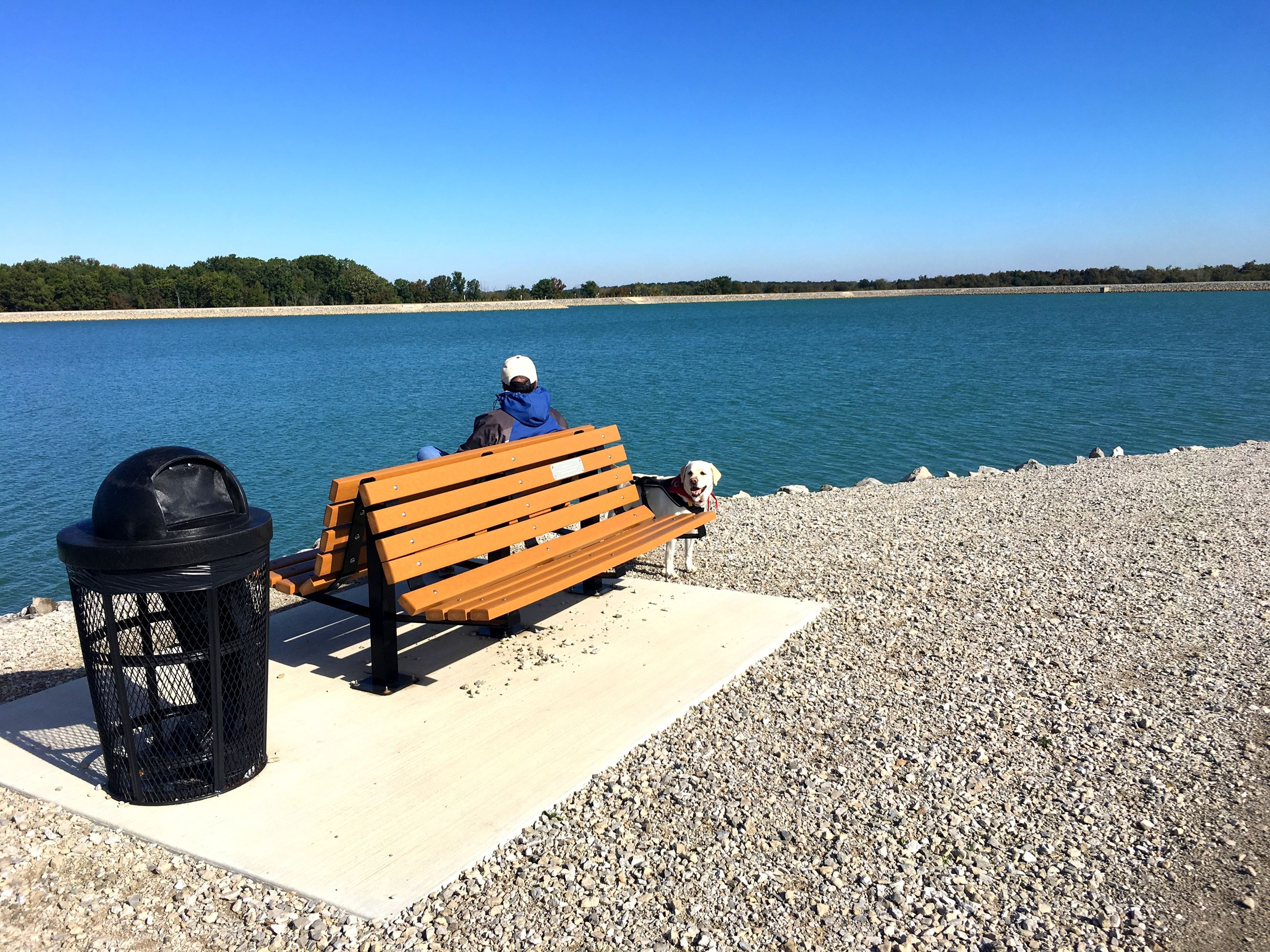 Photo of person sitting on bench at reservoir