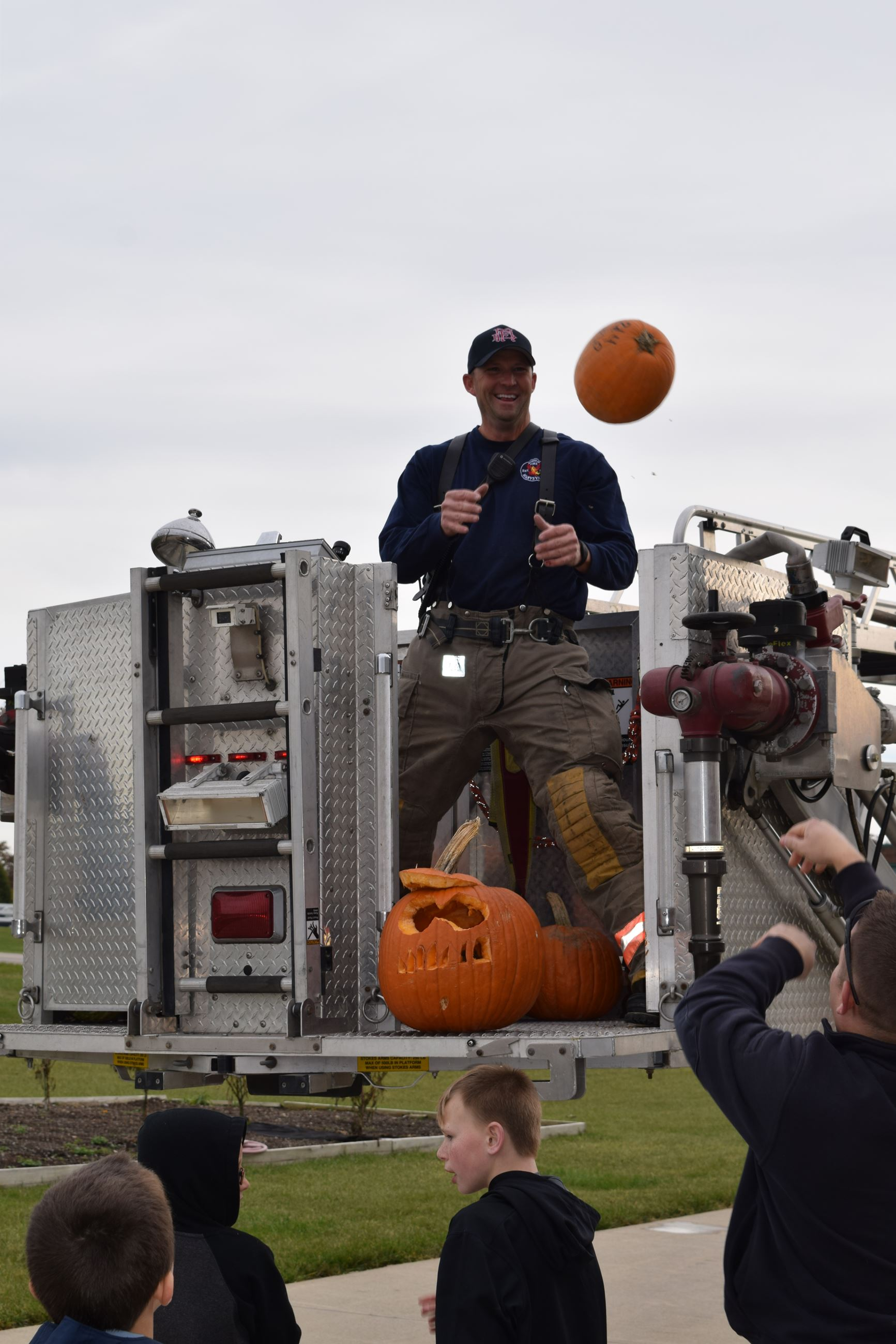 Photo of Firefighters loading pumpkins onto fire truck