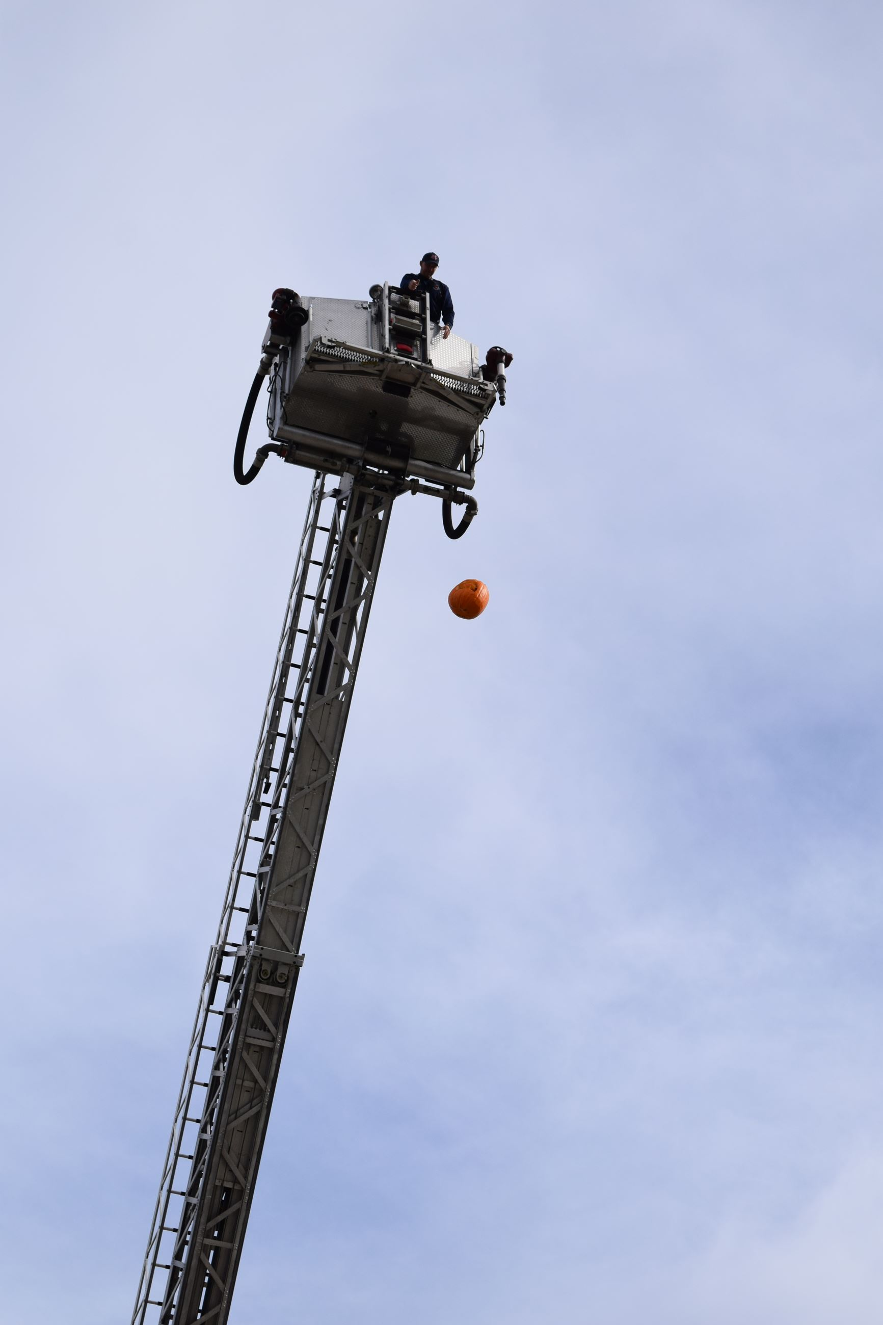 Photo of firefighter dropping pumpkin from ladder truck