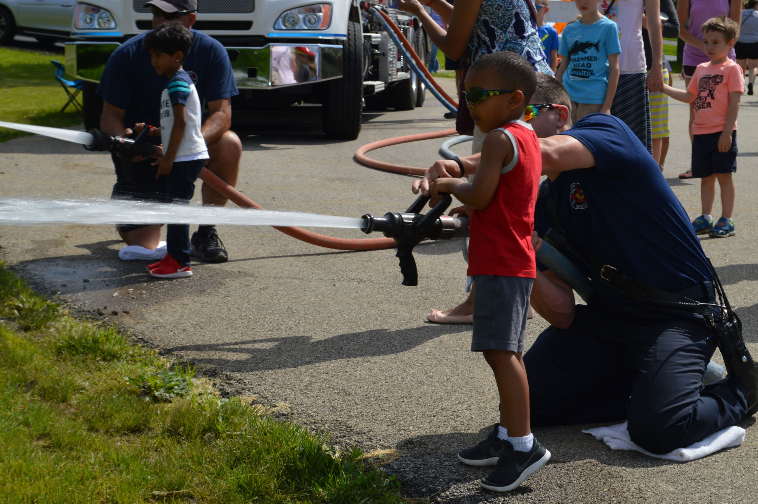 Photo of kids using fire hose to put out pictures of fires