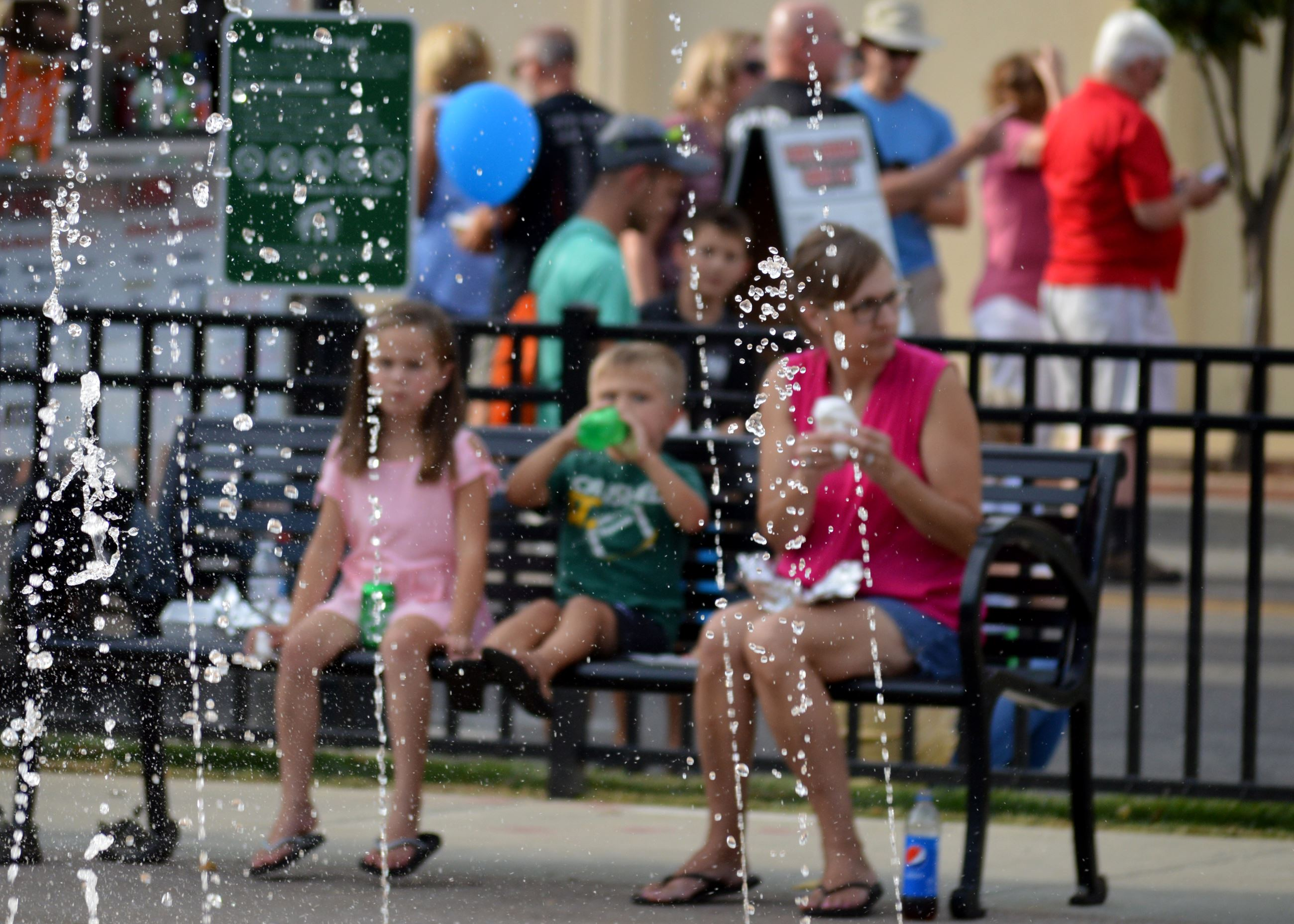 Family sitting on bench near splash pad fountain