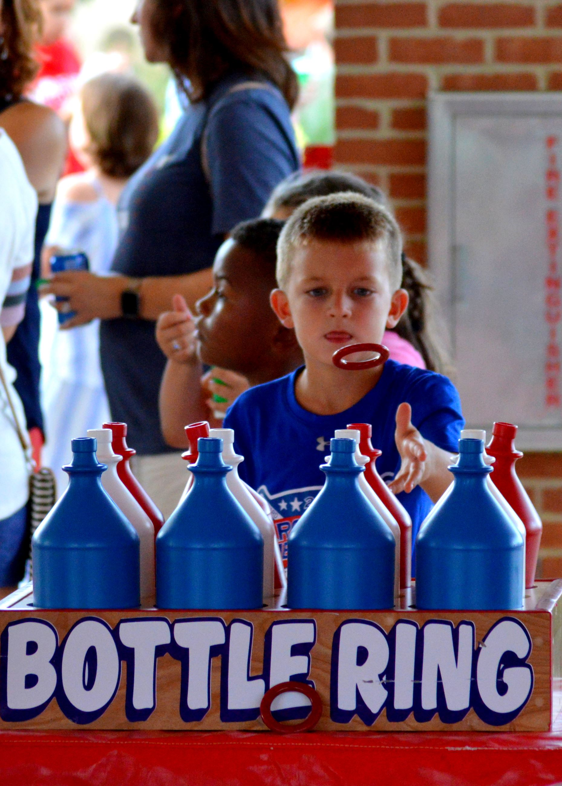 Boy tossing rings onto bottles