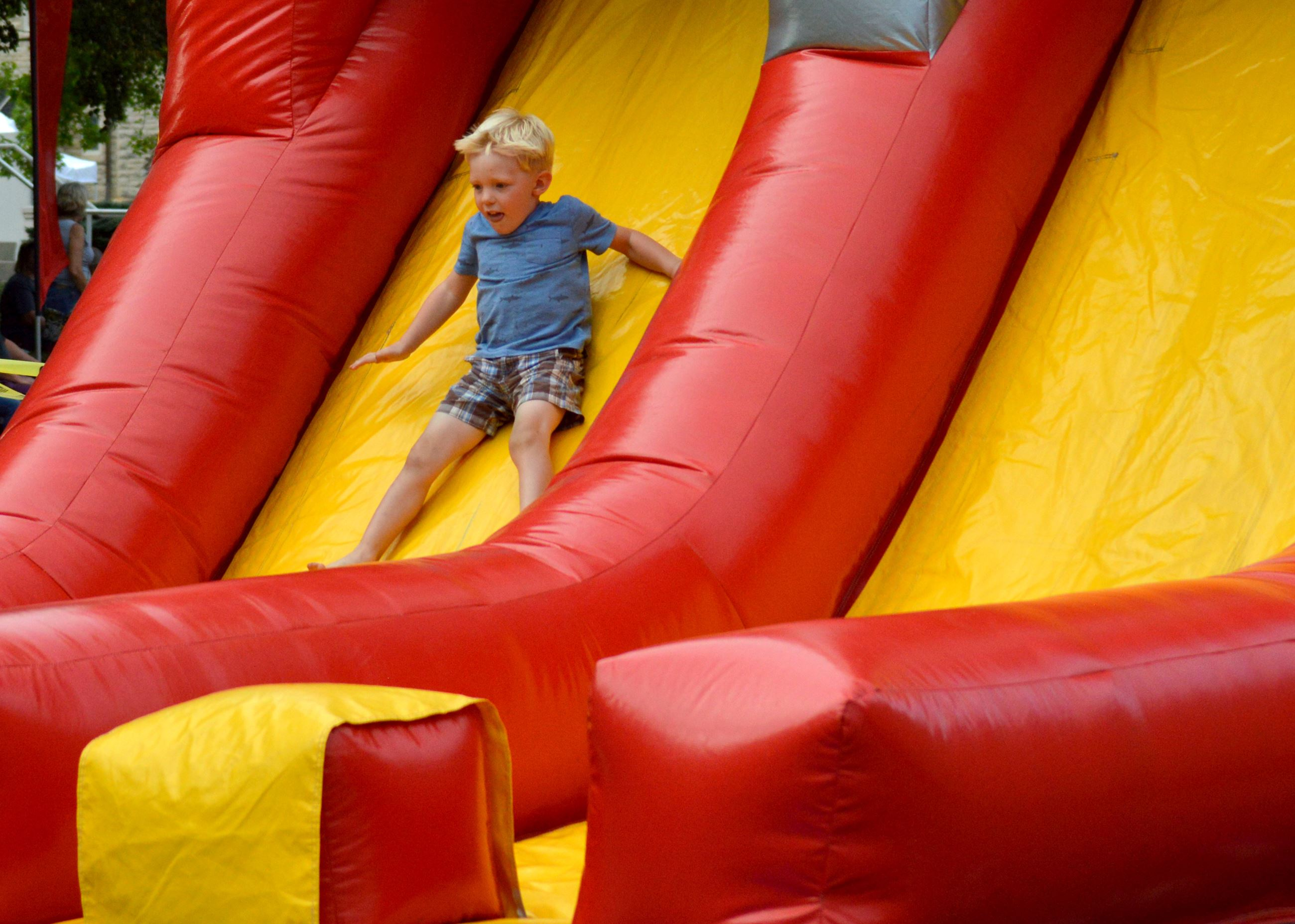 Boy sliding down slide at end of obstacle course